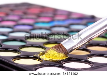 Closed-up professional make-up brush on yellow make-up shadows
