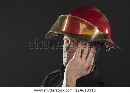 Closed up shot of a tired fireman over a black background