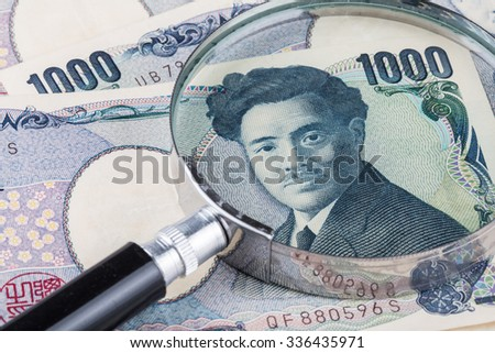 Closed-up Stack of Japanese currency yen or Japanese banknotes with magnifying glass