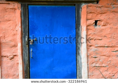 closed up the blue wood door with brick wall, in village Nepal