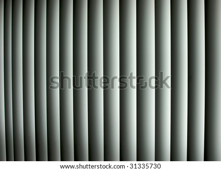 Closed vertical window blinds with sun light shining through make up this abstract image, Suitable as a background or wallpaper. - stock photo