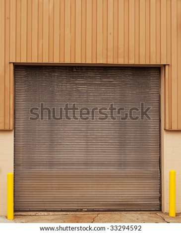 closed warehouse door with yellow posts - stock photo