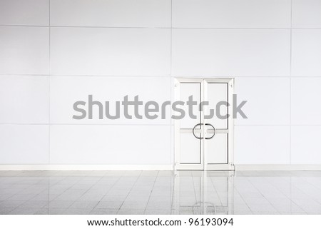 Closed white door, white wall and white marble floor in empty office - stock photo