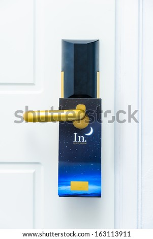 closed white door with a Do Not Disturb sign on the handle - stock photo