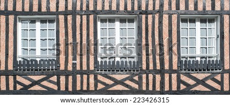 Closed windows of timber frame building with red brick texture wall in Beuvron en Auge, Nomandy, France - stock photo
