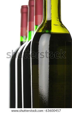 Closed wine bottles in row on white background.