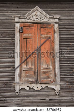 Closed wood window on aged wooden wall with closed shutters - stock photo