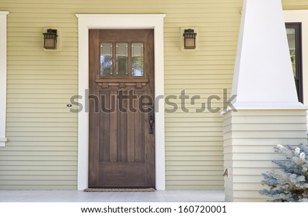 Closed wooden door of a home with yellow siding in daytime. - stock photo