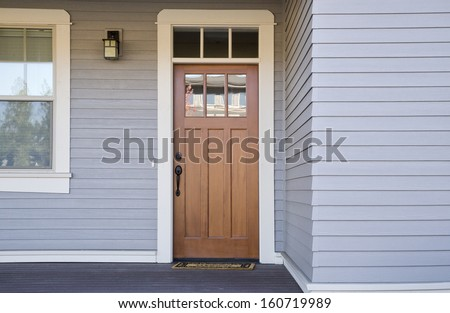 Closed wooden front door of a house during daytime - stock photo