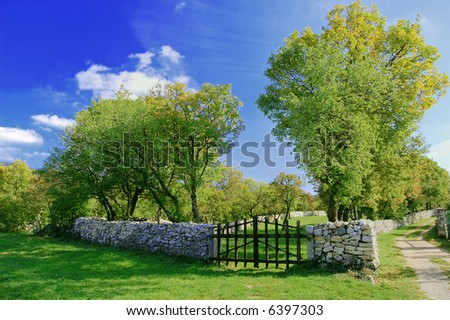 Closed wooden gate in a stone wall - stock photo