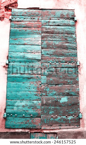 Closed wooden shutters with peeling paint and nail heads. Stucco wall house. - stock photo