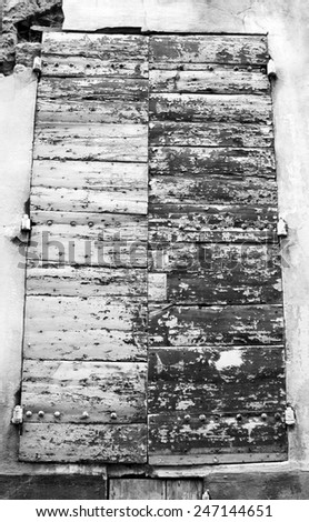 Closed wooden shutters with peeling paint and nail heads. Stucco wall house. Aged photo. Black and white. - stock photo