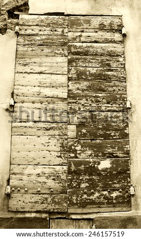 Closed wooden shutters with peeling paint and nail heads. Stucco wall house. Aged photo. Sepia. - stock photo