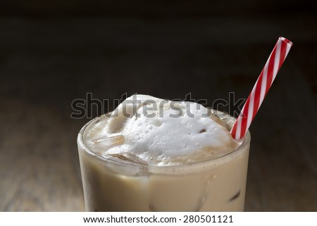Closee up detail of a Glass of Ice coffee with a red and white straw