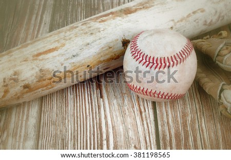 Closely cropped image of old, worn baseball equipment on a wooden background including a bat, mitt and ball. Vintage filter applied. Copy space. Concept of spring training, playoffs or summer. - stock photo