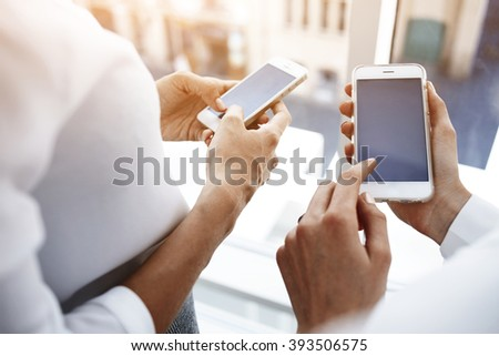 Closely image of woman`s hand is holding cell telephone with copy space screen for your advertising text message, while her friend near dials the number on smart phone. Two female are using cellphones - stock photo