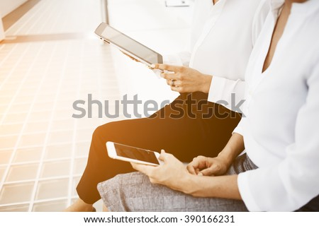 Closely of a two office people are reading something on web page via cell telephone and touch pad gadgets. Women are using their smart phone and digital tablet, while are waiting business meeting - stock photo