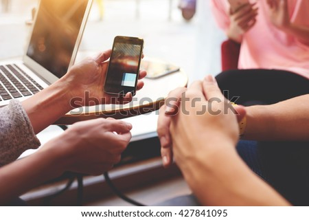 Closely of hand is holding cell phone with copy space screen for your advertising content. Two person are watching video in internet via mobile phone, while are sitting near open net-book on the table - stock photo
