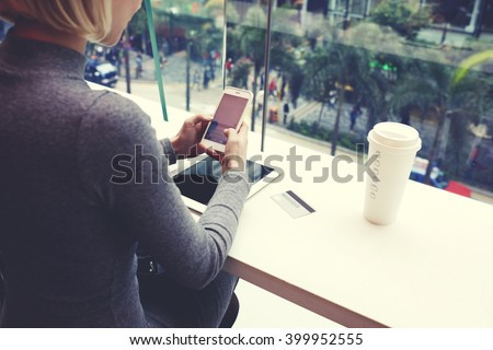 Closely of woman is typing text message on cell telephone, while is resting in coffee shop of modern shopping center in New York. Young hipster girl is chatting in social network via mobile phone - stock photo