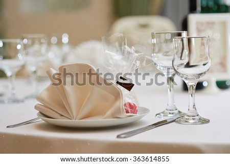 Closer look. Closeup shot of a restaurant table with empty glasses and a plate with a napkin on top