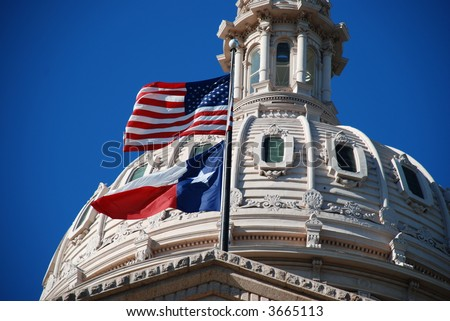 closer look of the Texas state capitol building's dome with waving flags of the United States and Texas - stock photo
