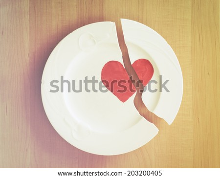 Closeup above view of a broken white ceramic china plate with red heart on wood board background.  Concept for divorce, relationships, friendships.  Vintage camera filter. - stock photo