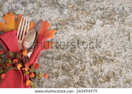 Closeup Above View of a Pretty Fall Place Setting with Silver fork, knife, and spoon on Rustic Stone Background with Room or Space for Copy, text, your words.  Horizontal Looking Down  - stock photo