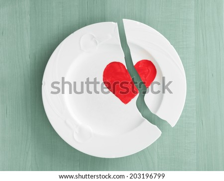 Closeup above view of broken white ceramic china plate dish with a red heart painted on it, on teal blue wood board background.  Concept or metaphor for divorce, relationships, friendships,  - stock photo