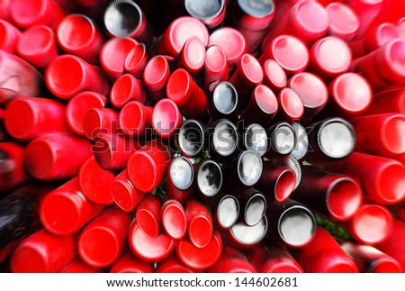 Closeup abstract view of a stack of glass bottle painted in red color stuck into a crate, for the concept of bottleneck. - stock photo