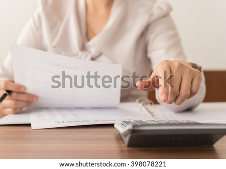 Closeup accountant women check the numbers on the balance sheet. - stock photo