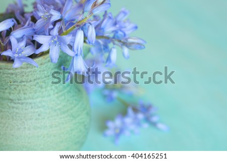Closeup Aerial of Soft and Dreamy Lavender Lilly Flowers Spilling out of a Green Stoneware Vase with a Teal Blue Wood Horizontal Background with room or space for copy, text, your words to the side  - stock photo