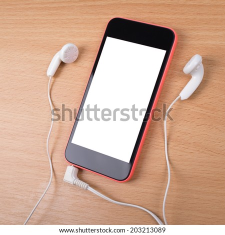 Closeup aerial view of smart phone with white isolated screen. Smart phone with earphones on wooden surface. Mock-up concept of black and red smart phone with headphones on wooden table background. - stock photo