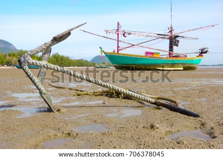 closeup anchor with fishing boat on the coast