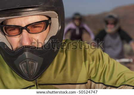 Closeup and cropped view of a male mountain biker in a helmet and protective eyewear. In the background are two other bikers. Horizontal shot. - stock photo