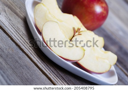 Closeup angled horizontal photo of fresh apple slices, on white plate, with whole apple and rustic wood in background   - stock photo