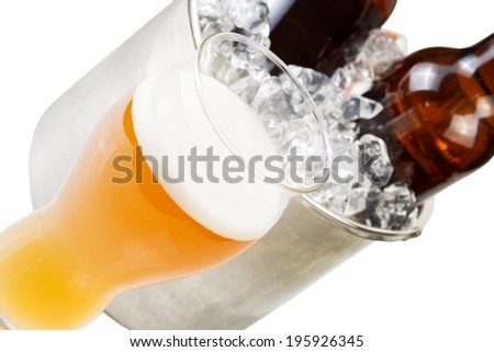 Closeup angled horizontal photo of freshly poured beer in large glass and bottled beer in stainless steel bucket filled with ice isolated on white