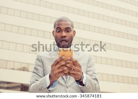 Closeup anxious shocked young business man looking at phone seeing bad news or photos with disgusting emotion on face isolated on corporate office background. Human emotion, reaction, expression - stock photo