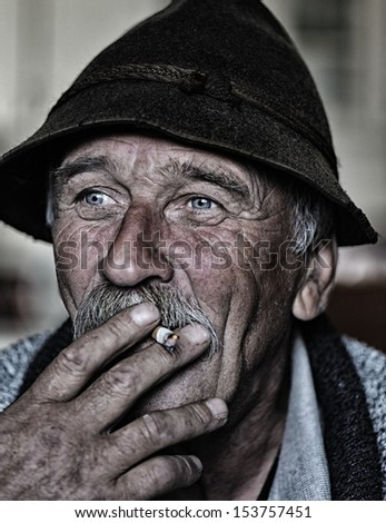 Closeup Artistic Photo of Aged Man With Grey Mustache Smoking Cigarette  - stock photo