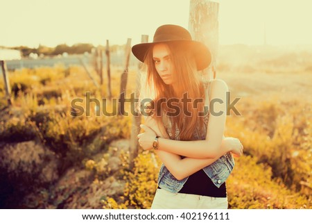 closeup attractive beautiful brunette woman with fluffy long hairs posing  in the Park, autumn meadow,sunset light,in a black hat,denim vest and shorts,red lips,spring mood,sadness outdoor portrait - stock photo