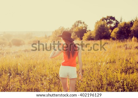 closeup attractive beautiful brunette woman with fluffy long hairs posing standing in a Park, autumn meadow, sunset light, in a black hat, a denim vest and shorts,spring mood, sadness,outdoor portrait - stock photo