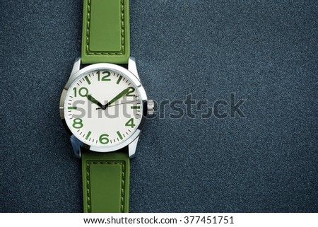 closeup automatic men watch with green wrist on dark background  - stock photo
