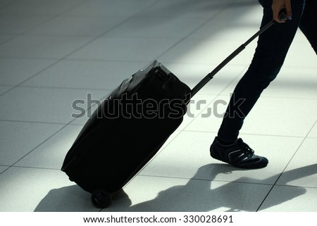 Closeup back view of female legs in jeans with black rolling suitcase wheeled travel bag trolley case moving over airport terminal floor tile background, horizontal picture - stock photo