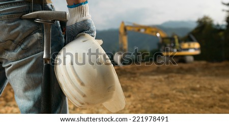 closeup back view of male engineer standing on construction site holding white hardhat - stock photo