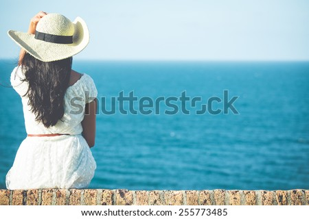 Closeup back view of woman sitting in white dress and hat looking out towards blue ocean and sky, isolated sea background - stock photo
