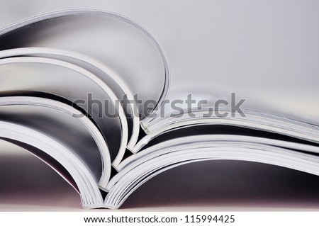 Closeup background of a pile of old magazines with bending pages. Small shallow dof. - stock photo