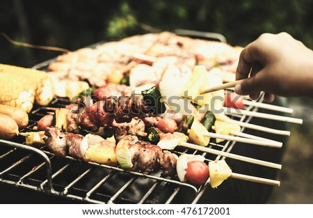 Closeup barbecue on child hand in asian barbecue party, vintage image.
