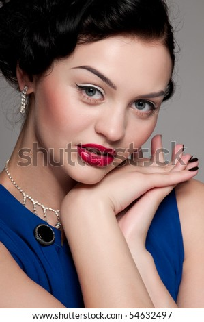 Closeup beautiful emotional glamour woman with red lips. Blue dress, black nails and beads. Vogue