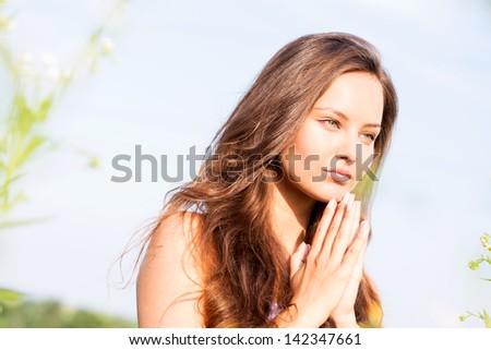 Closeup beautiful  young woman who prays - stock photo
