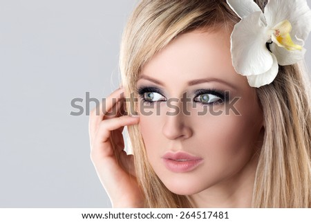 Closeup Beauty Female Face Spa. Beautiful Young Woman Model with White Flower Orchid in Her Blonde Hair touching Cheek. - stock photo