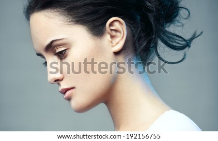 Closeup beauty portrait of a young beautiful brunette woman. Muse. Profile, looking down. - stock photo